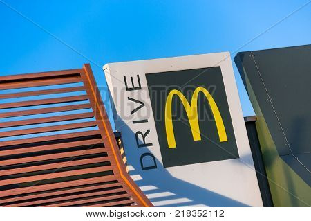 Beaulieu France - October 26 2015: McDonald's yellow and red drive-thru logo advertising sign placed on white board against clear sky. McDonald's Corporation is a fast-paced American fast-food chain founded by businessman Ray Kroc in 1952.