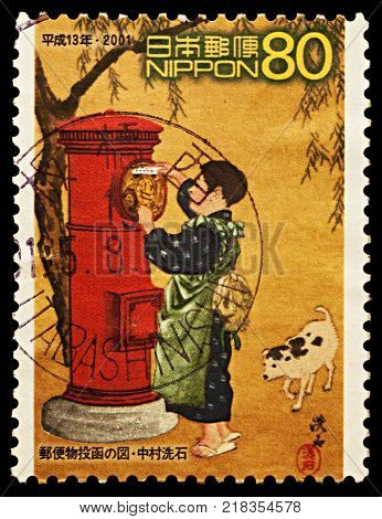 Moscow Russia - December 15 2017: A stamp printed in Japan shows Japanese boy posting mail dedicated to the 100th Anniversary of Red Cylindrical Letter Boxes circa 2001