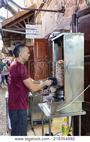 Acre Israel November 03 2017 : The seller cuts electric shawarma from the grill for customers on the market in the old town of Acre in Israel