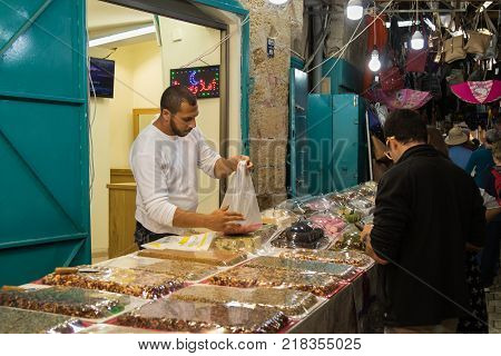 Acre Israel November 03 2017 : The seller sells sweets to the customer on the market in the old town of Acre in Israel