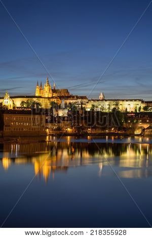 View of the lit Prague (Hradcany) Castle, Charles Bridge (Karluv most) and their reflections on the Vltava River in Prague, Czech Republic, in the evening.