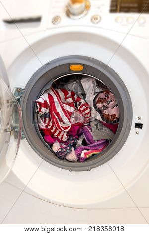 Close-up of an open washing machine full of dirty laundry ready to be washed.