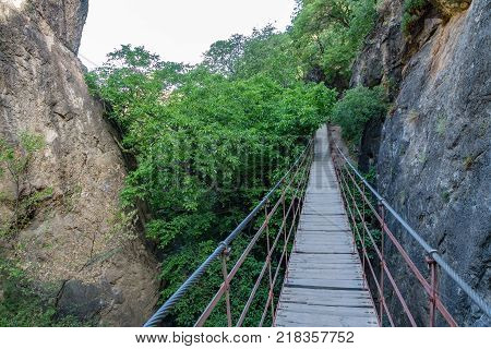 Wide angle of Iron and wooden suspension bridge in canyon between high rocks