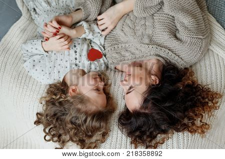 Small curly girl and her mother lie together in bed, looks at each other with great love, enjoy togetherness. View from above of affectionate mother and daughter. Children and parents concept.