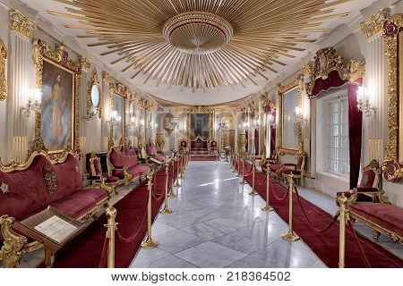 Cairo, Egypt - December 2, 2017: Throne Hall at Manial Palace of Prince Mohammed Ali Tewfik with ornate ceiling inspired by the old flag of the ottoman empire gold plated armchairs and red carpets