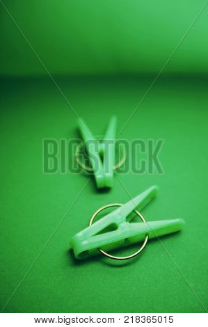 Green plastic clothes clothes pegs on a bright one-color green background. Top view. Blurred background. Household supplies isolated. top view. Close up