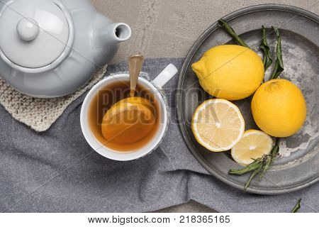 Cup of tea with lemon on table close-up. Healthcare traditional medicine and flu concept - tea cup with lemon. Hot tea with lemon treatment of colds flu and runny.