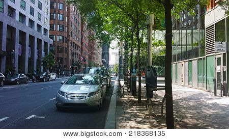 Montreal Quebec Canada - 20 July 2016: Electric cars charging at recharging station undert green trees in summertime as editorial