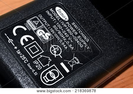 BANGKOK THAILAND - DECEMBER 15: Power specifications and various certification labels on a small AC to DC power adapter.