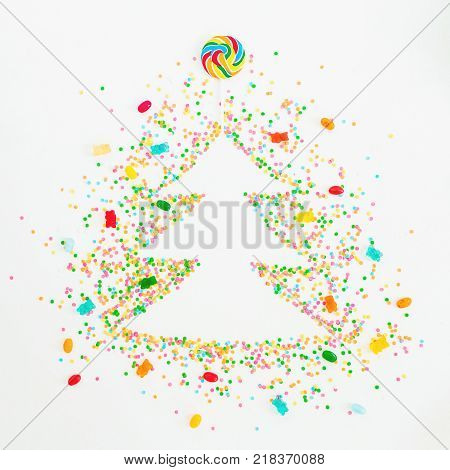 Creative Christmas tree made of colorful bright confetti, marmalade and candy on white background. Flat lay, top view poster