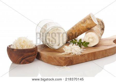Fresh and grated horseradish in wooden bowl with parsley on wooden cutting board. Horseradish sauce. Isolated on white background