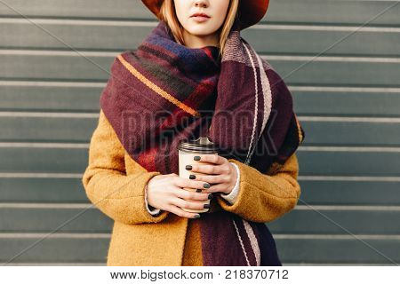 partial view of woman in autumn jacket and hat with coffee to go in hands