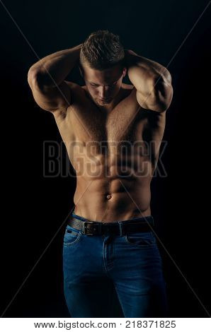 Man sportsman show muscular torso in jeans on black background. Bodybuilder with bare torso six pack ab biceps triceps muscles. Sport bodybuilding fitness. Healthy lifestyle concept.