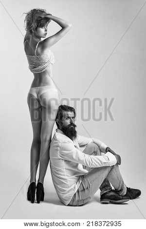 handsome bearded man with long beard and moustache on serious face sitting near young pretty girl with sexy legs and buttocks in lingerie in studio isolated on white background copy space