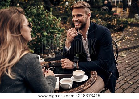 So what do you think about that? Handsome young man in smart casual wear smiling while having a conversation with young woman in restaurant outdoors