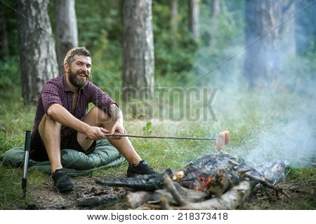 Hipster man with beard happy smile and roast sausages on stick on bonfire in forest. Summer camping hiking vacation. Picnic barbecue cooking food concept.