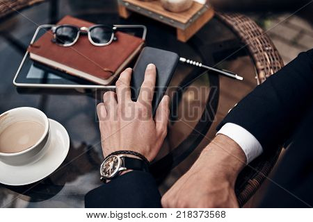 Busy working day. Close up top view of young man in smart casual wear having a little coffee break while sitting in restaurant outdoors