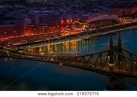 The magic panorama of the city at dusk river bridge and city lights. Budapest Hungary tilt-shift effect toned