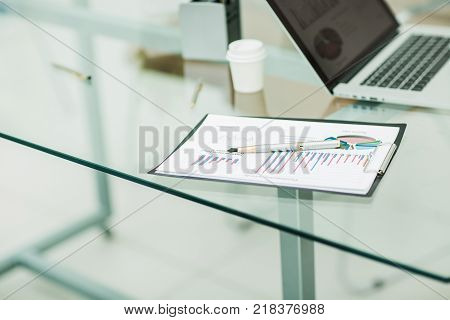 success concept in business - a financial chart, pen and notebook at the workplace of the businessman.the photo has a empty space for your text