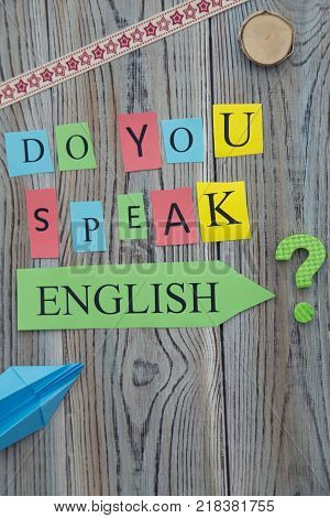 Do you speak English inscription of printed letters on a wooden background, educational concept