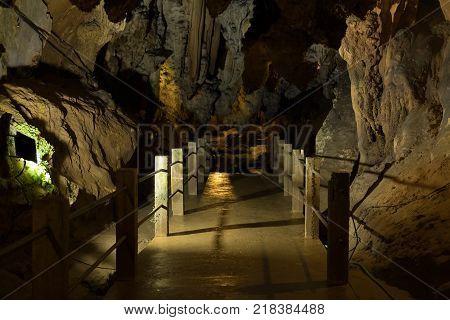 Footbridge In Stone Cave. Bridge In Cavern With Stalactite.
