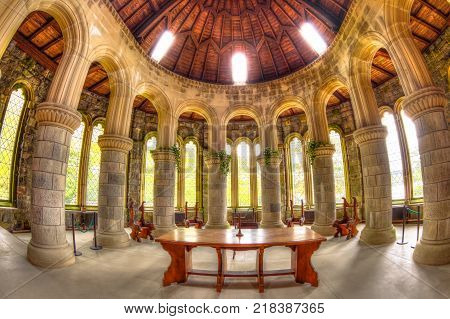 Argyll, Scotland, United Kingdom - June 1, 2015: marble pillars, arched glass windows, and wooden cross altar in the apse Saint Conan's Kirk gothic church in Argyll town in Scottish Highlands.