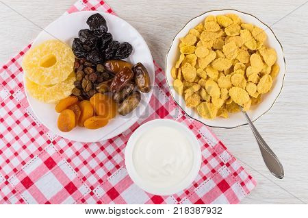 Corn flakes in bowl sour cream dried fruits in plate on wooden table napkin. Top view