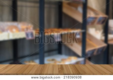 bakery shop with different kind of bread bun pastry on shelf. blur background with wood table for display or montage product