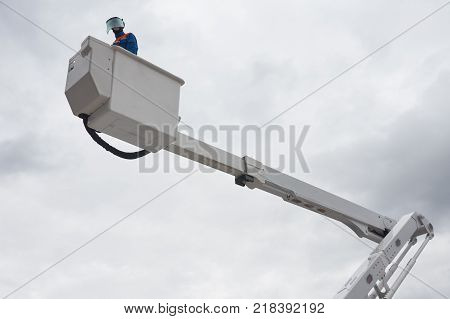 An electrician in protective uniform works on insulated aerial platform designed to work safely on electric power lines. Electrician is a dummy.