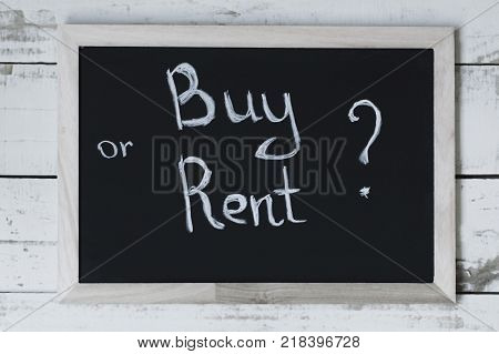 Buy or rent concept. Handwritten text on blackbord. Choosing between renting (leasing) and buying property