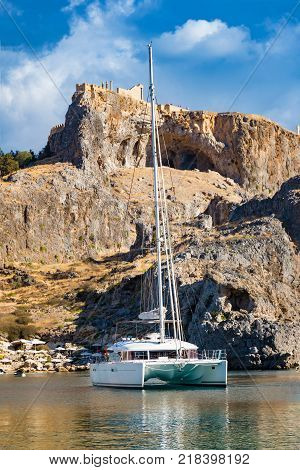 Catamaran in St. Paul´s bay cloudy blue sky Lindos acropolis in background (Rhodes Greece)