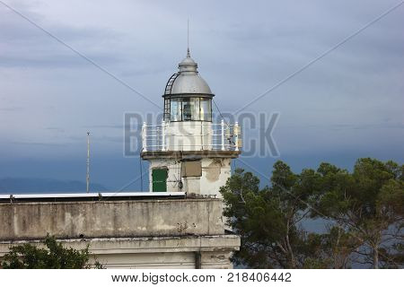 Old lighthouse with balcony against dark sky. Sea lighthouse surrounded by trees.