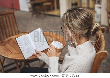 Woman reading a paper book with a cup of coffee in outdoor cafe hobby