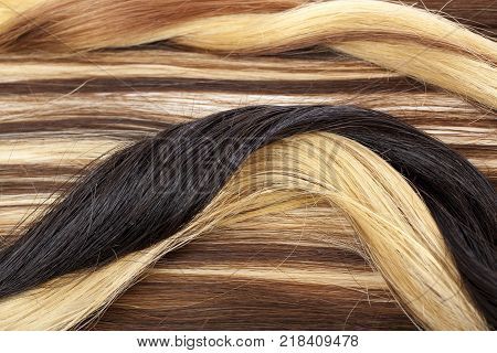Human hair european hair weft for hair extension. Brown blonde hair texture closeup pattern. Shiny real dyed tail.