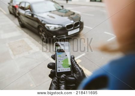 GREENWICH LONDON UNITED KINGDOM - MAR 10 2017: Woman waiting for the UBER taxi cab on British street with message Completing a trip nearby on screen phone