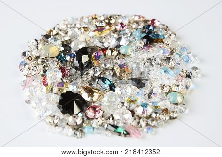 Pile of beautiful colorful jewelry diamonds on white background, close up. Pile of crystals close-up. Jewelry, luxury, treasure concept