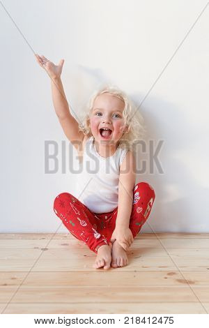Adorable small female child wears pyjamas, sits on wooden floor raises hands as happy to see affectionate parents, isolated over white background. Cheerful cute smiling little kid indoor at home