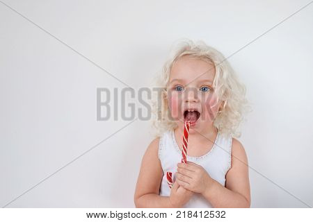 Horizontal shot of attractive blue eyed female kid has rough cheeks, looks thoughtfully aside, licks red and white sweet caramel cane, isolated over white background. Lovely small child indoor.