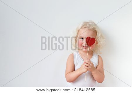 Blue eyed pretty small kid dressed casually, has fun indoors, covers eye with heart stick, glad to spend free time with her parents, isolated over white background with copy space for your text.