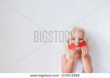 Indoor shot of pretty blonde female with blue eyes, holds two paper red hearts, poses against white background with copy space for your advertisment. Beautiful adorable preschooler isolated
