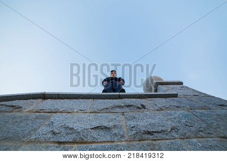 Young man standing on top of a wall leaning out to look at the ground while doing parkour.