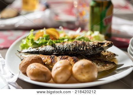 Grilled sardines with baced potatoes. raditional portuguesse dish. Blurred