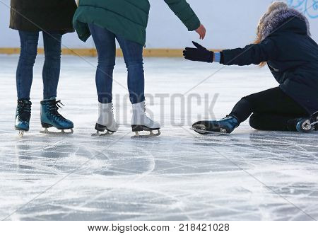 people help to get up after a fall skating on the ice rink