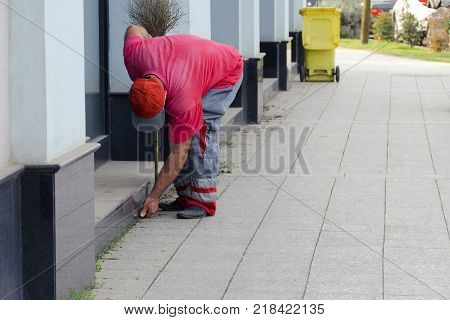 Cleaning of a city street - the worker the yard keeper in a uniform collects garbage by hands near a building behind it there is a trash can.