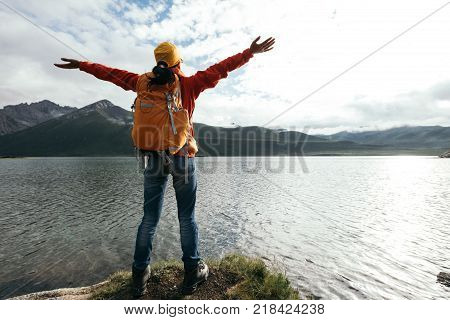 cheering young backpacking woman open arms on high altitude lakeside