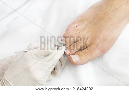 Female foot in the process of pedicure procedure in a beauty salon close-up.