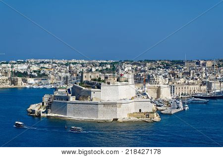 View to the ancient limestone walls and towers of Fort St. Angelo from Upper Barrakka Gardens view across the Grand Harbor Valletta Malta.