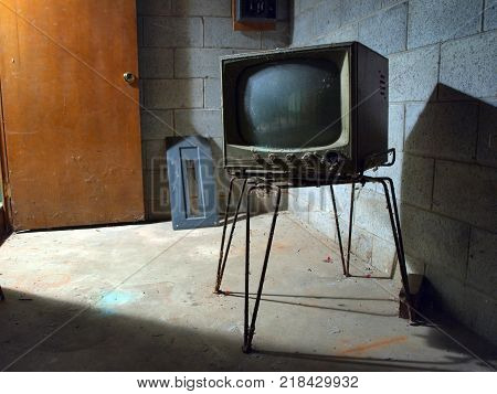 An old TV from the 1950s sitting abandoned and forgotten in a basement.
