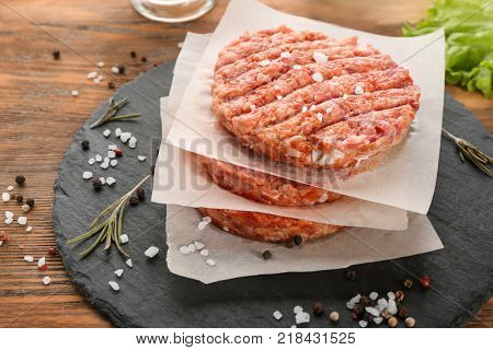 Slate plate with raw burger patties on table