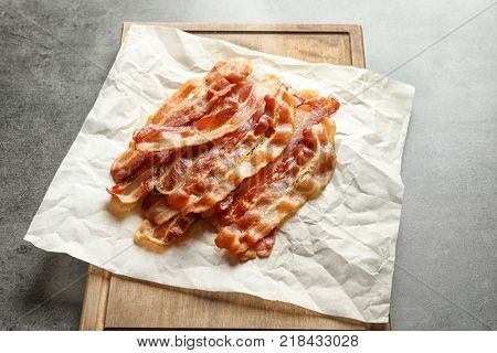 Board with cooked bacon rashers on table